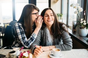 Two smiling friends sharing secret in coffee talk