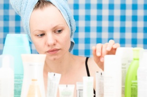 Girl is choosing cosmetics in bathroom